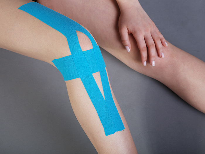 young pretty woman with sports taping on knee